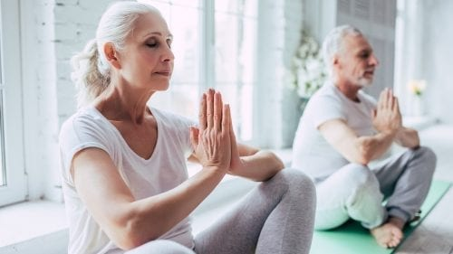 male and female senior practicing meditation