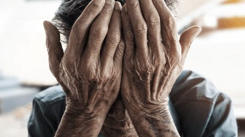 man with hands in face- elder abuse