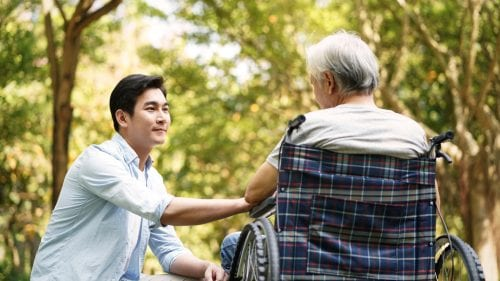 caregiver- Son holding dad in wheelchair hand